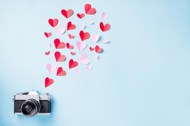 Fotocamera retrò vintage e cuori di elementi volanti di carta tagliati carta regalo di auguri