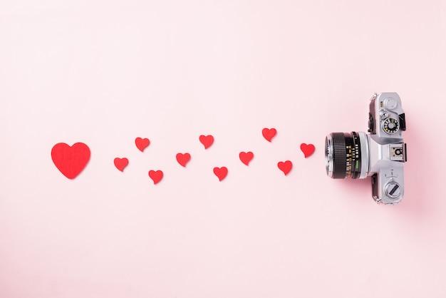 La retro macchina fotografica d'annata e la cartolina d'auguri rossa della composizione nei cuori amano il giorno di biglietti di s. valentino