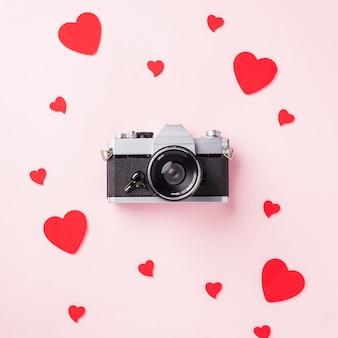 La retro macchina fotografica d'annata e la cartolina d'auguri della composizione nei cuori rossi amano il giorno di biglietti di s. valentino