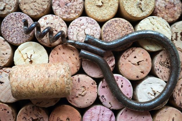 Cavatappi vintage arrugginito con tappo singolo sullo sfondo di molti tappi per vino