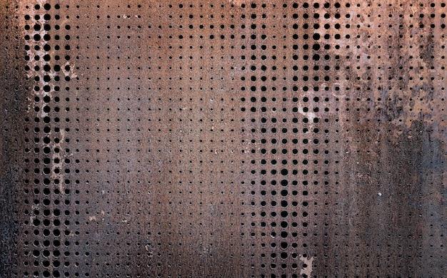L'acciaio arrugginito d'annata del grunge decorato perforando una priorità bassa di struttura della parete