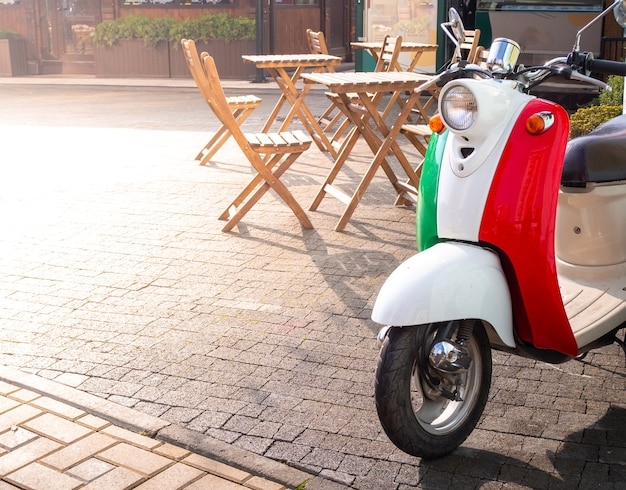 Scooter vintage colorato come bandiera italiana sulla piazza soleggiata vicino a street cafe