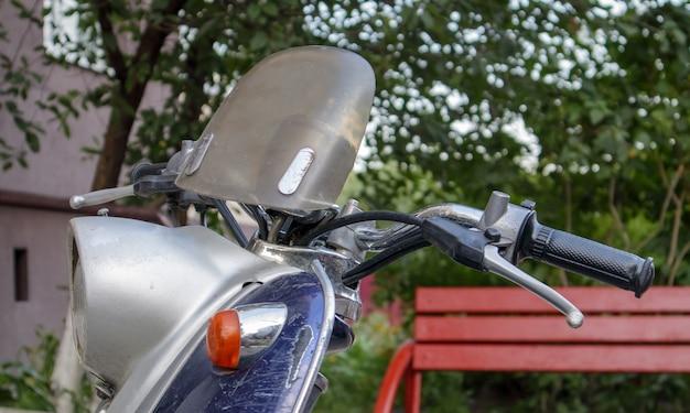 Supporto per scooter o mini moto d'epoca all'aperto. un popolare mezzo di trasporto. il volante di un vecchio ciclomotore blu con un sedile marrone.
