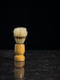 Pennello da barba vintage per la rasatura sul tavolo di pietra su sfondo nero. set per la cura del viso di un uomo.
