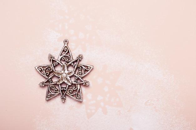 Fiocco di neve d'argento d'annata del giocattolo di natale su fondo rosa.
