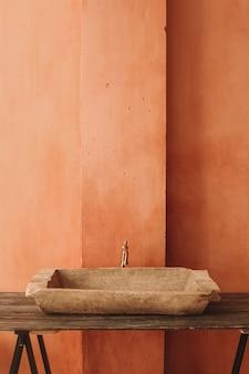 Lavandino dell'annata su una mensola di legno alla parete arancione del grunge