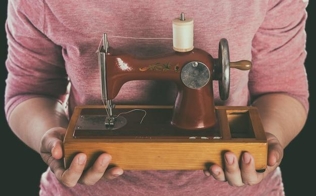 Piccola macchina da cucire vintage in mano di una donna