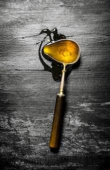 Cucchiaio vintage con miele naturale. sulla tavola rustica nera.