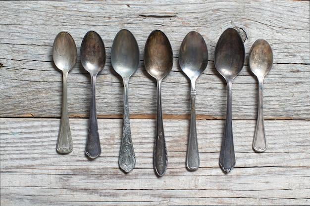 Cucchiai vintage con patina sul vecchio tavolo in legno