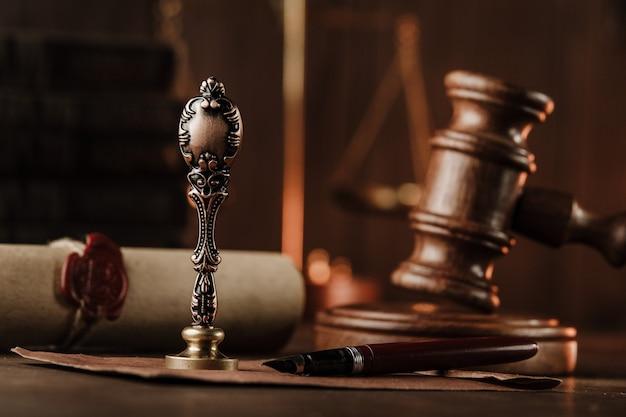 Timbro vintage e primo piano del martelletto del giudice su una scrivania in legno