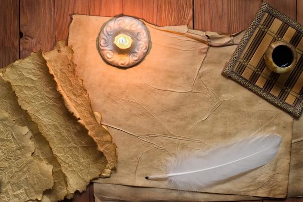 Natura morta vintage con piuma, carta vecchia e candela accesa su sfondo di tela