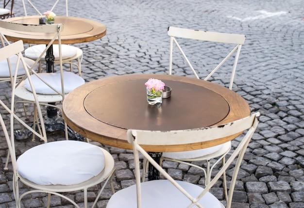 Tavola e sedie d'annata nel terrazzo del caffè della via, alacati, turchia
