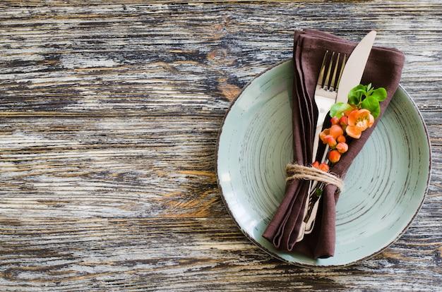 Regolazione della tabella dell'annata con delicati fiori sul tavolo squallido rustico.