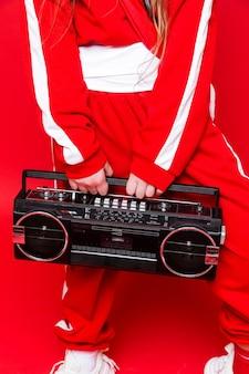 Registratore a nastro vintage nelle mani di una ragazza. la ragazza è vestita con una tuta da ginnastica rossa. studio girato. foto verticale