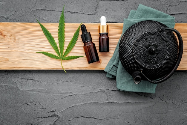 Teiera vintage con tisana di cannabis impostata su sfondo concreto.