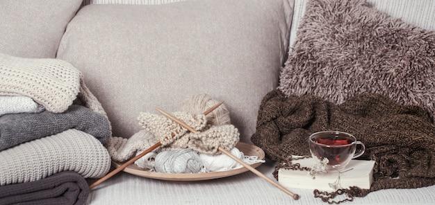 Ferri da maglia e fili di legno d'annata su un accogliente divano con cuscini e una calda tazza di tè
