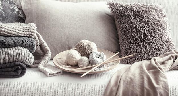 Ferri da maglia vintage in legno e fili per lavorare a maglia su un accogliente divano con cuscini e maglioni