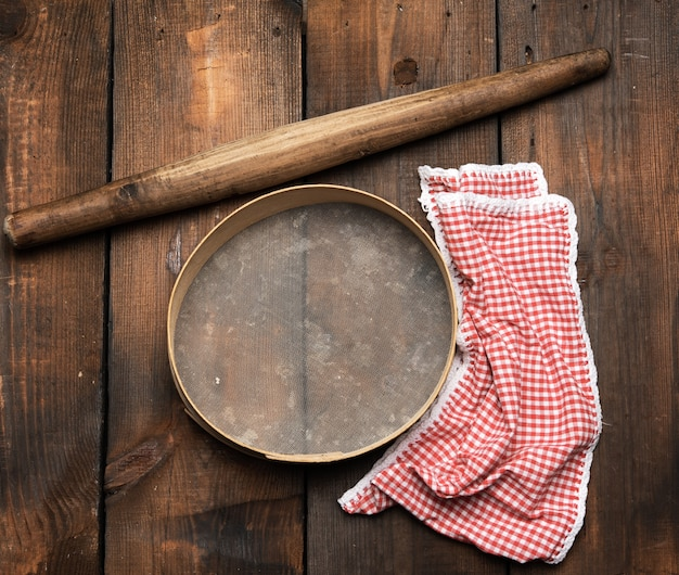 Mattarello in legno d'epoca e un setaccio rotondo, tovagliolo rosso, vista dall'alto, utensili da cucina per fare la pasta