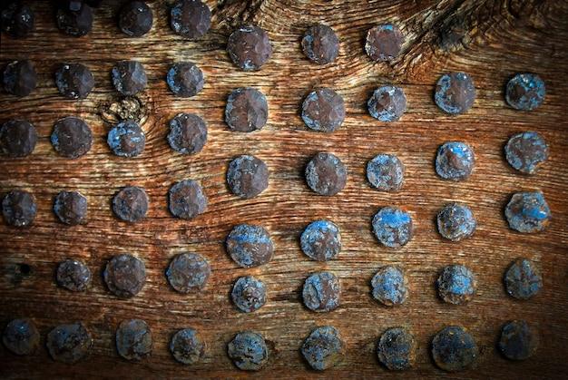 Superficie in legno vintage con messa a fuoco selettiva di rivetti in metallo