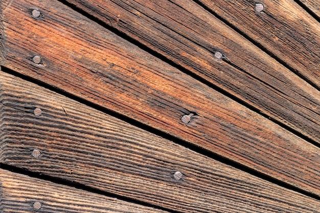 Struttura della parete in legno d'epoca. tavole di legno esposte all'aria con il primo piano dei chiodi