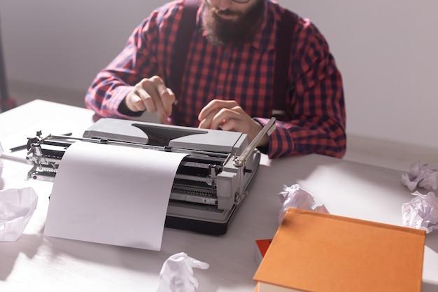Concetto d'annata, scrittore e hipster - giovane scrittore alla moda che lavora alla macchina da scrivere