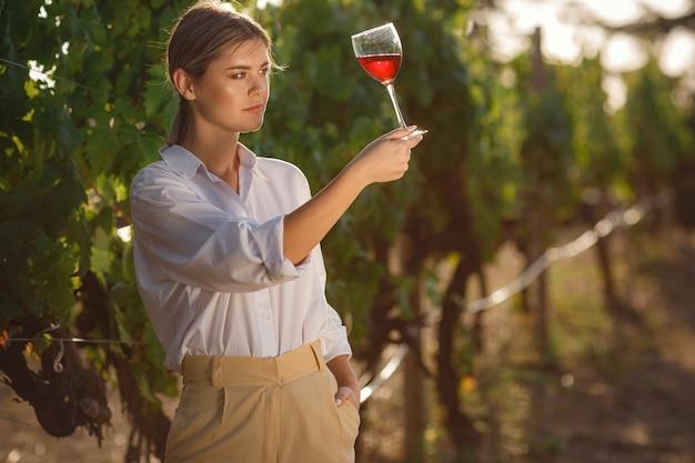 Donna vignaiolo degustazione di vino rosso da un bicchiere in un vigneto