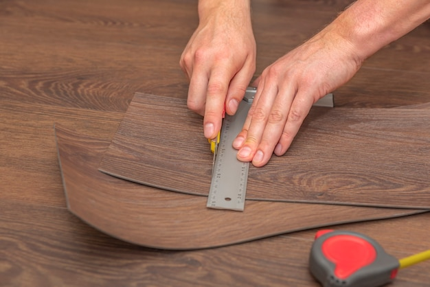 Installazione di pavimenti in vinile e taglio a mano con un pavimento riscaldato marrone coltello
