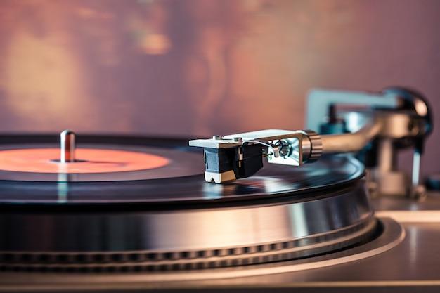 Giradischi in vinile, luci da discoteca-bokeh. ago sul disco in vinile.