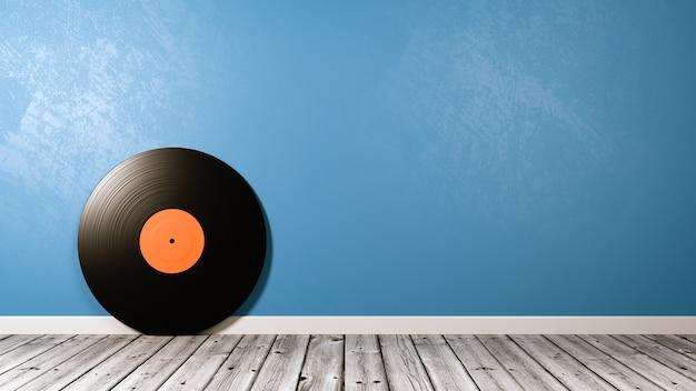 Disco in vinile sul pavimento in legno contro il muro