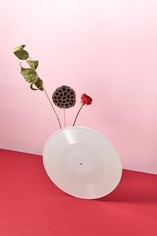 Disco retrò in vinile decorato con rami secchi e un fiore rosso su sfondo rosso rosa bicolore