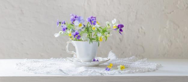 Fiori viola in tazza bianca su sfondo bianco