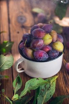 Prugne viola e verdi in tazza di metallo bianco con foglia verde e gocce d'acqua sullo sfondo di legno marrone. raccolta dei frutti estivi.