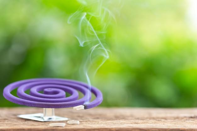 Repellente della zanzara viola sulla tavola di legno con il fondo verde dello spazio della luce della sfuocatura