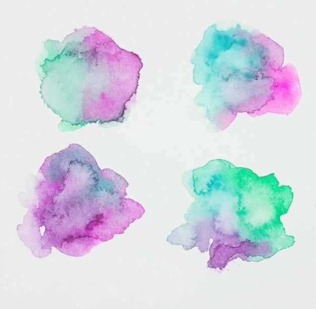 Macchie di vernice viola e verdeggianti su carta bianca