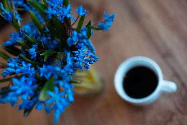 Fiori di viole sullo sfondo del tavolo in legno e tazza di caffè.