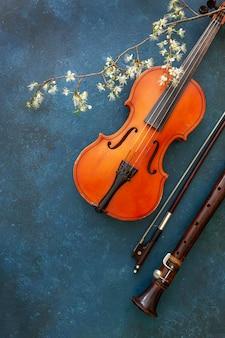 Violino, arco e flauto con un ramo di ciliegio in fiore