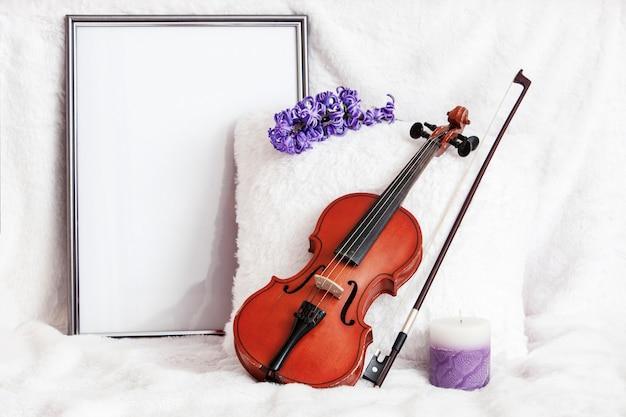 Violino, giacinto, candela e cornice per foto con posto per il testo sullo sfondo di un cuscino bianco e un copriletto morbido e accogliente.