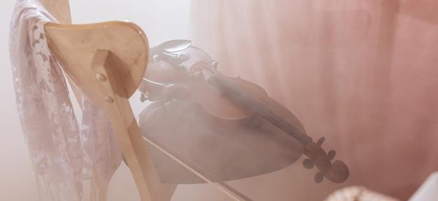 Il violino giace su una sedia in una sala per banchetti nella nebbia