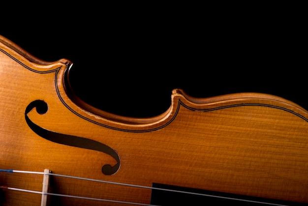 Strumento di musica del violino del primo piano dell'orchestra isolato sul nero
