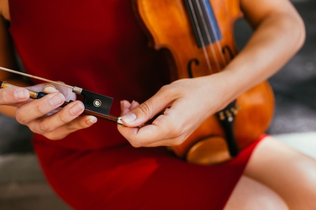 Accordatura del violino. musica classica. la donna controlla il suo strumento prima di suonarlo concept