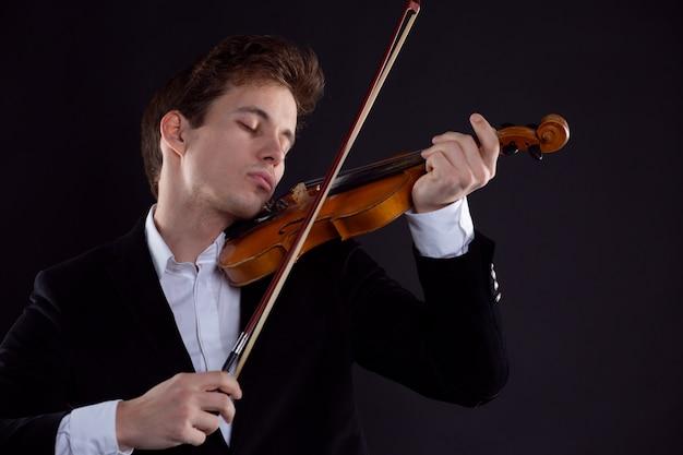 Un violinista suona emotivamente il violino in un concerto dell'orchestra sinfonica
