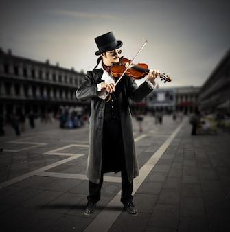 Il violinista suona in una piazza con gente che cammina