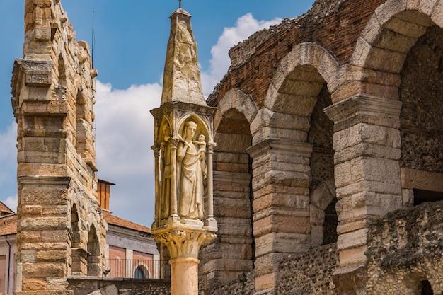 Vergine maria con gesù bambino, statua del xv secolo in piazza bra a verona, italia
