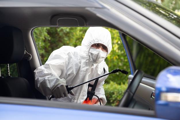 L'uomo virologo che indossa i kit dpi uccide batteri e virus all'interno dell'auto servizio di sterilizzazione e pulizia covid nel concetto di auto