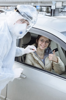 Un virologo o un medico che indossa indumenti protettivi ignifughi ppe preleva un campione di un test pcr con un tampone di cotone da una guidatrice nella sua auto.