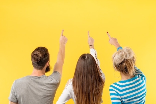 Spazio della copia dell'annuncio virtuale. vista posteriore di tre persone che punta con le dita a un oggetto immaginario. muro giallo.