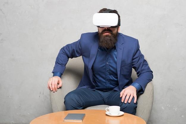 Ufficio virtuale e spazio di lavoro. l'uomo d'affari si siede sedia indossa hmd esplora la realtà virtuale o ar. i partner commerciali interagiscono nella realtà virtuale. nuova opportunità. le aziende implementano la tecnologia moderna.