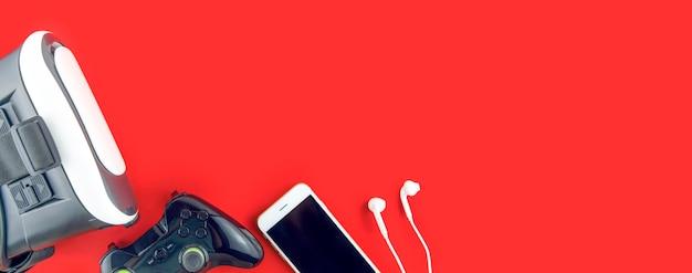 Occhiali per realtà virtuale 360, game pad e telefono su un tavolo rosso