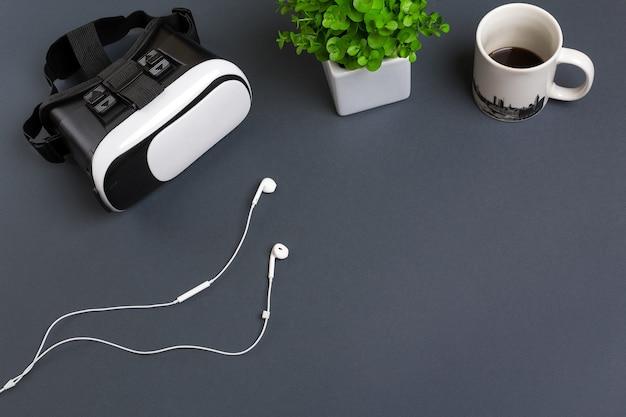 Occhiali e cuffie per realtà virtuale su uno sfondo grigio vista dall'alto