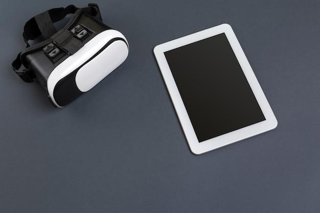 Occhiali e tablet per realtà virtuale su uno sfondo grigio vista dall'alto
